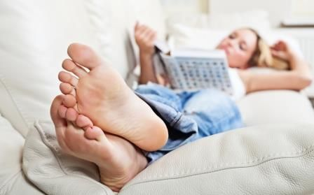 Close up sockless feet of a Calgary woman lounging on a couch